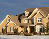 Beautiful home in winter. Beautiful multi story home in winter, lit by golden morning light stock photo