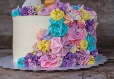 Beautiful homemade cake in the form of a unicorn. With cream colored flowers on a wooden table royalty free stock image
