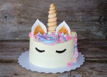Beautiful homemade cake in the form of a unicorn. With cream colored flowers on a wooden table royalty free stock photos