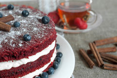 A beautiful homemade cake and a glass cup of tea on a linen surface decorated with blueberries, hips, lace and cinnamon sticks Royalty Free Stock Image