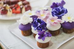 Beautiful Homemade Cupcakes With Purple, White And Pink Marzipan Flowers On Top Royalty Free Stock Photos