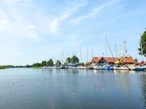 River Minija ,sailing ships and homes, Lithuania. Beautiful homes , sailing ships and river Minija in Village Minija royalty free stock images