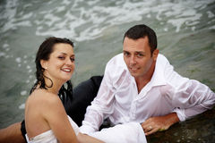 Beautiful honeymooners - bride and groom portrait. Beutiful couple of honeymooners posing at seashore in their wedding outfits stock images