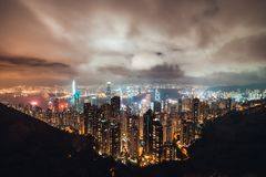 Beautiful Hong Kong island cityscape, aerial night view from Victoria Peak in cloudy storm weather. Asia tourism concept royalty free stock image
