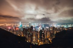 Beautiful Hong Kong island cityscape, aerial night view from Victoria Peak in cloudy storm weather royalty free stock images