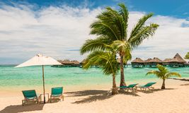 Beautiful French Polynesian beach with chairs and umbrella. Relaxation and vacation concept. stock images