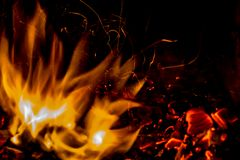 A beautiful horizontal texture of a burning fire on a black background with sparks. Is in the photo Stock Photo