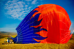 Hot Air Balloon with Blue Flames Deflating on Ground, Beautiful Scenery