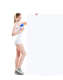 Beautiful hot young sporty woman with dumbbell standing nearby the billboard Stock Image