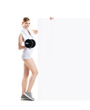 Beautiful hot young sporty woman with a dumbbell standing nearby the billboard Stock Images