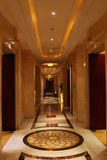 The light is downy hotel corridor. Smooth floor with marble mosaic pattern, wall lights and configured to warm color Royalty Free Stock Images