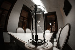 Beautiful hourglass on brown wood table with shadow Royalty Free Stock Image