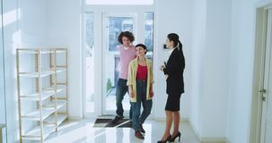 Beautiful house agent showing a new modern house to a charismatic young couple she gesticulating with hands smiling she. Have a discussion with her client. shot stock footage