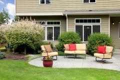 Beautiful house with backyard sitting area. Royalty Free Stock Image