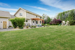 Beautiful house backyard with well kept lawn and patio area. Beautiful house backyard with well kept lawn, patio area and playground at the background stock photography