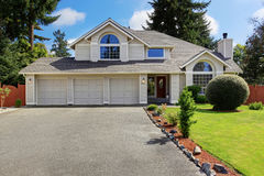 Beautiful house exterior with curb appeal. Luxury house exterior with tile roof. House with three car garage and front yard landscape Royalty Free Stock Photo