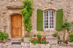 A beautiful house facade in Provence, with a wooden door and French window with green shutters. A street view of a quaint French provincial house facade with stock photos
