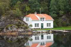 Beautiful house in the reflection on the shore of the pond royalty free stock image