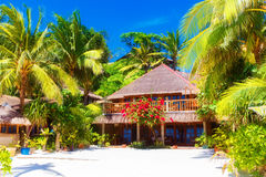 Beautiful house to a reed roof standing on a white, sandy beach Stock Photo