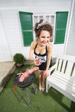Beautiful housemaid fry sausage on brazier near house Royalty Free Stock Photography