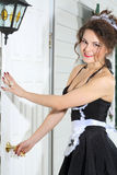 Beautiful housemaid opens front door of house. Stock Photography