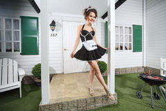 Beautiful housemaid poses near country house. And barbecue with sausages Stock Photos