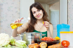 Beautiful housewife cook vegetables with oil Stock Photography