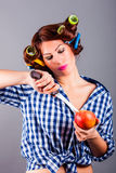 Beautiful housewife with curlers holding apple and the knife. Portrait of beautiful housewife with curlers holding apple and the knife royalty free stock images