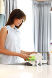 Beautiful housewife doing dishes Stock Image