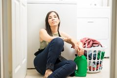 Bored young woman sitting on floor in laundry room. Beautiful housewife feeling restless sitting in laundry room with back support of washing machine with Stock Photos