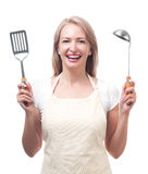 Beautiful housewife with ladle and spatula. Isolated on white ba Stock Images