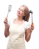 Beautiful housewife with ladle and spatula. Isolated on white ba Stock Photography