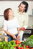 Beautiful housewife with man cooking with fresh vegetables at ho Stock Photos