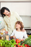 Beautiful housewife with man cooking with fresh vegetables in ki Stock Image