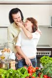 Beautiful housewife with man cooking with fresh vegetables at ki Royalty Free Stock Images