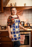 Beautiful housewife posing against gas stove with saucepans Stock Images