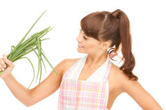 Beautiful housewife with spring onions over white Stock Images