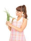 Beautiful housewife with spring onions over white Royalty Free Stock Images