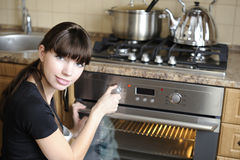 Beautiful housewife switching the oven royalty free stock photo