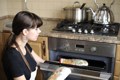 Beautiful housewife using the oven stock photography