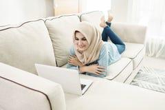 Beautiful housewife wearing hijab enjoy browsing on laptop in a