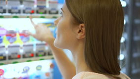 Beautiful hungry woman picking item out of vending machine in mall. Choosing unhealthy snacks being hungry stock footage
