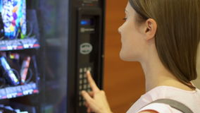 Beautiful hungry woman picking item out of vending machine in mall. Choosing unhealthy snacks being hungry