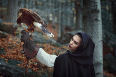 Beautiful huntress with hawk in a forest. Fantasy and falconry Royalty Free Stock Photos