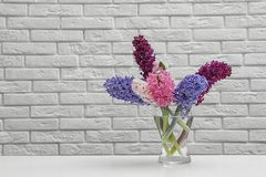 Beautiful hyacinths in glass vase on table against wall, space for text. Spring flowers. Beautiful hyacinths in glass vase on table against brick wall, space for stock image