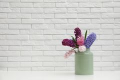 Beautiful hyacinths in metal can on table against wall, space for text. Spring flowers. Beautiful hyacinths in metal can on table against brick wall, space for royalty free stock images