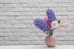 Beautiful hyacinths in pink vase on table against brick wall, space for text. Spring flowers stock photography