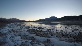 Beautiful ice covered river landscape in late autumn in the deep arctic circle wilderness with cold flowing water and mountain. Background stock video footage