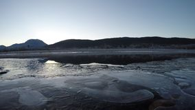 Beautiful ice covered river landscape in late autumn in the deep arctic circle wilderness with cold flowing water and mountain stock video footage
