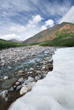 Beautiful ice on mountain river,valley,sky,clouds. Stock Photo